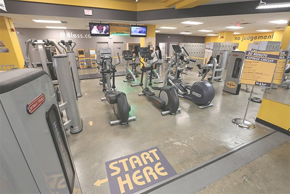 Grey and Yellow Fit4Less Gym with Concrete Flooring