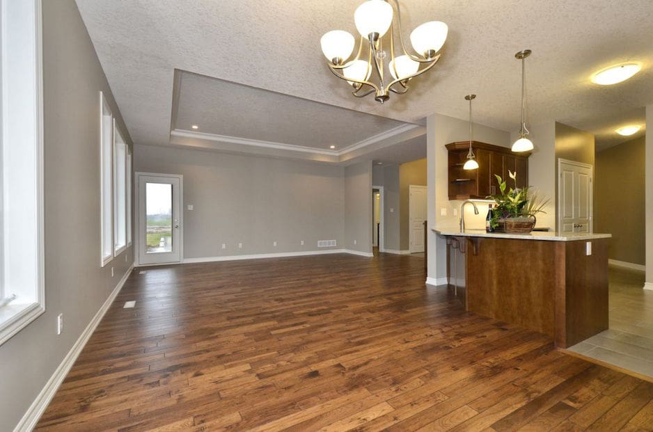 Dark hardwood floors in an open concept living room with a bright chandelier. A hardwood flooring installation or hardwood refinishing project in Ontario.
