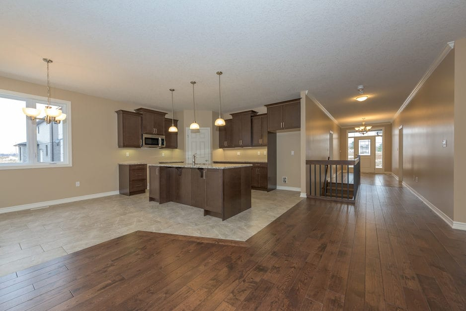 A hardwood flooring installation project: walnut stained solid hardwood floor or engineered hardwood floor with white baseboards in an open concept hardwood floored dining and tiled kitchen.