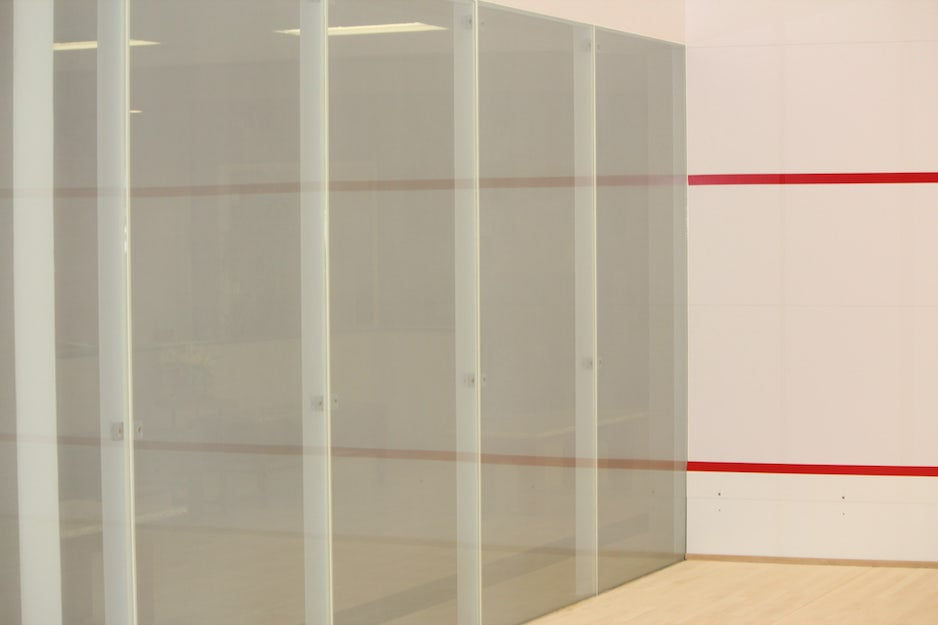 A squash court and court flooring installation project in Ontario. Squash court room with hardwood floor, glass backwall, specially constructed walls with line graphic work.