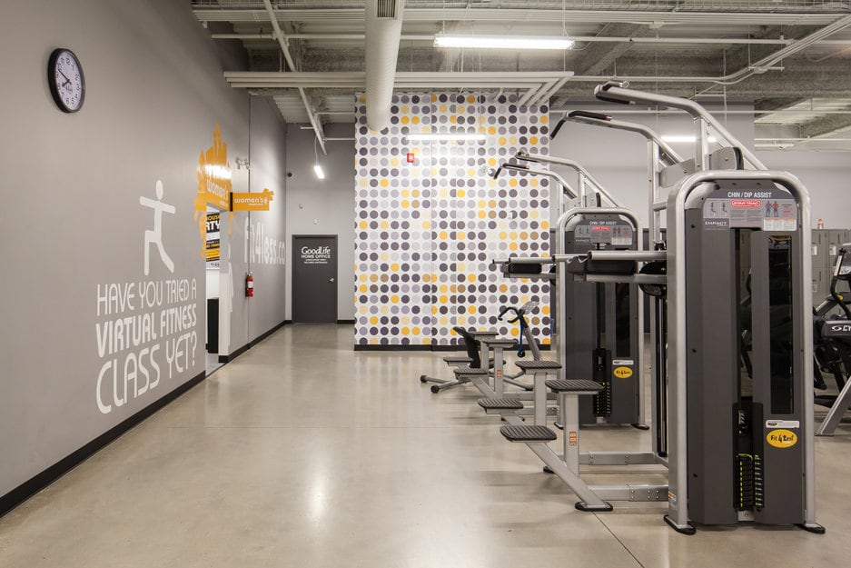 New concrete flooring project at Fit For Less Gym in London Ontario. Photo of gym exercise machine room with high polish concrete / cement flooring.
