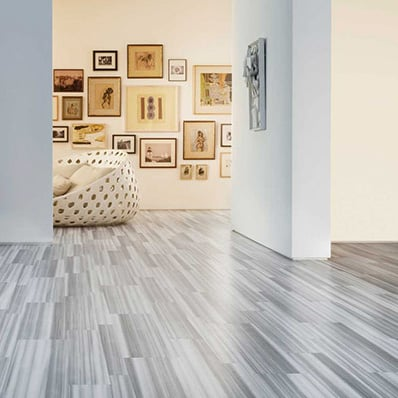 Grey hardwood flooring and collage of picture frames on the wall of a simple modern room.