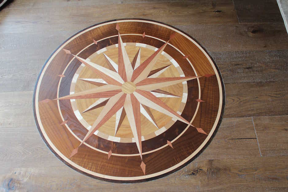 Hardwood flooring with a very intricate circular compass rose design with light, medium and dark wood elements meticulously cut and composed together. A work of hardwood art. Part of a Flatout flooring project in London Ontario.
