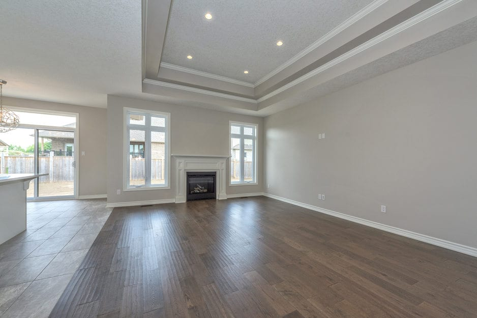 A London Ontario hardwood flooring installation project: walnut stained solid hardwood floor or engineered hardwood floor with white baseboards in a spacious open concept dining with a white fireplace.
