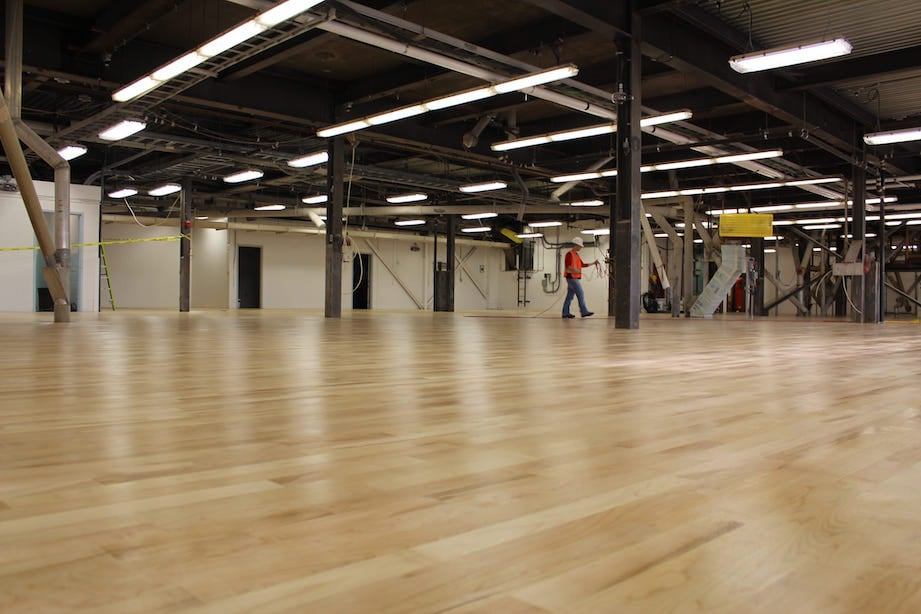 Hardwood flooring installation or wood floor finishing project in a large commercial / industrial space in the saltmine in Goderich, Ontario. A man at work walking on light hardwood floor.