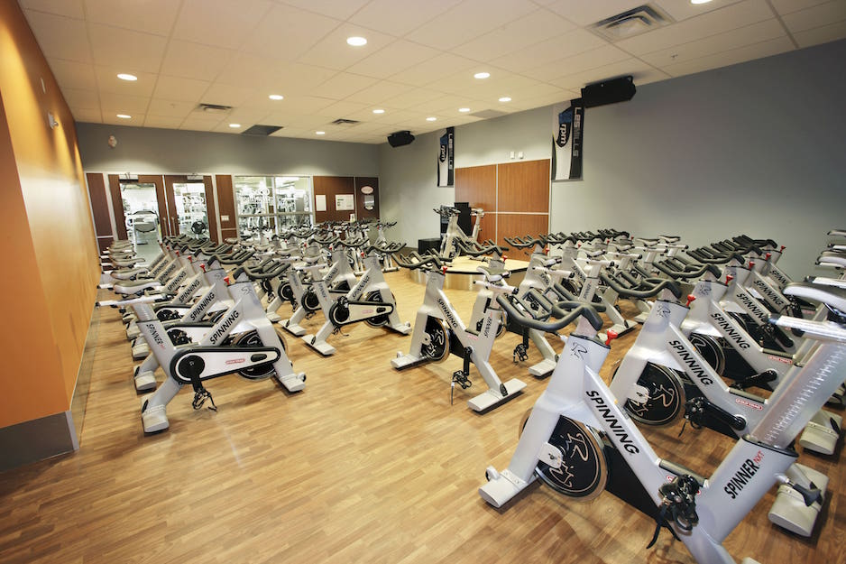 A flooring installation project in Ontario. Goodlife gym spinning equipment room with light-coloured hardwood or hardwood look LVT (luxury vinyl tile) flooring.