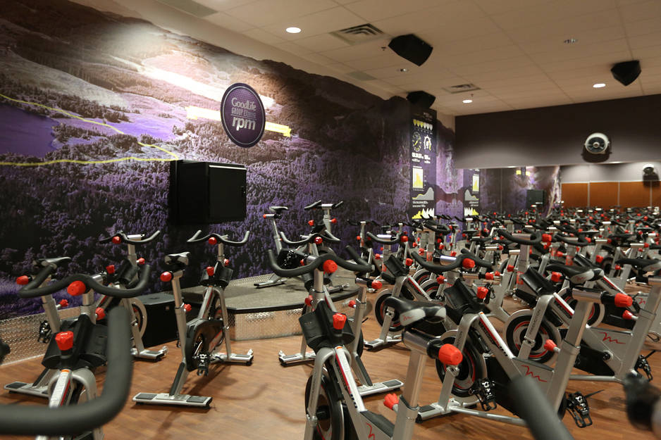 A gym floor / gym flooring installation project in Toronto. A Goodlife gym cycling room with hardwood or LVT flooring and purple mural on main wall.