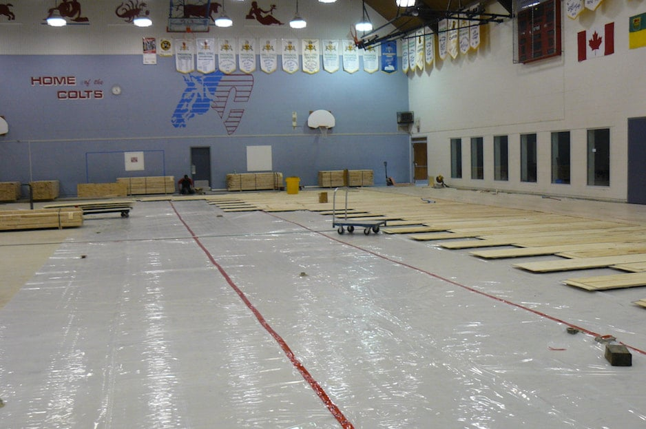 High school gym being renovated with new light hardwood flooring. Gym hardwood floor installation project.