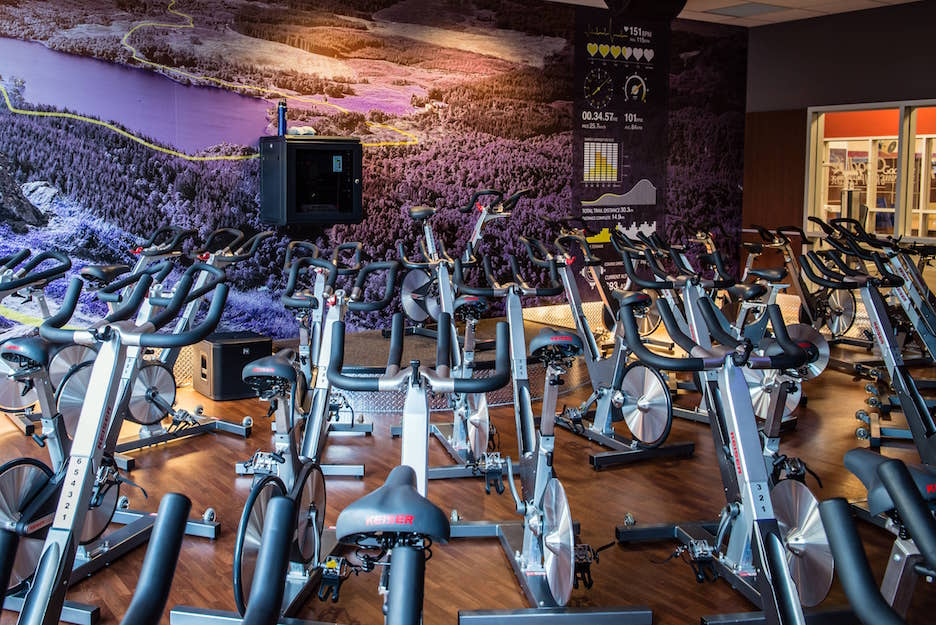 A gym flooring installation in Toronto or London. Goodlife spinning classroom with dark hardwood floors or wooden-look LVT (luxury vinyl tile) floors and a large landscape route map on the back wall.