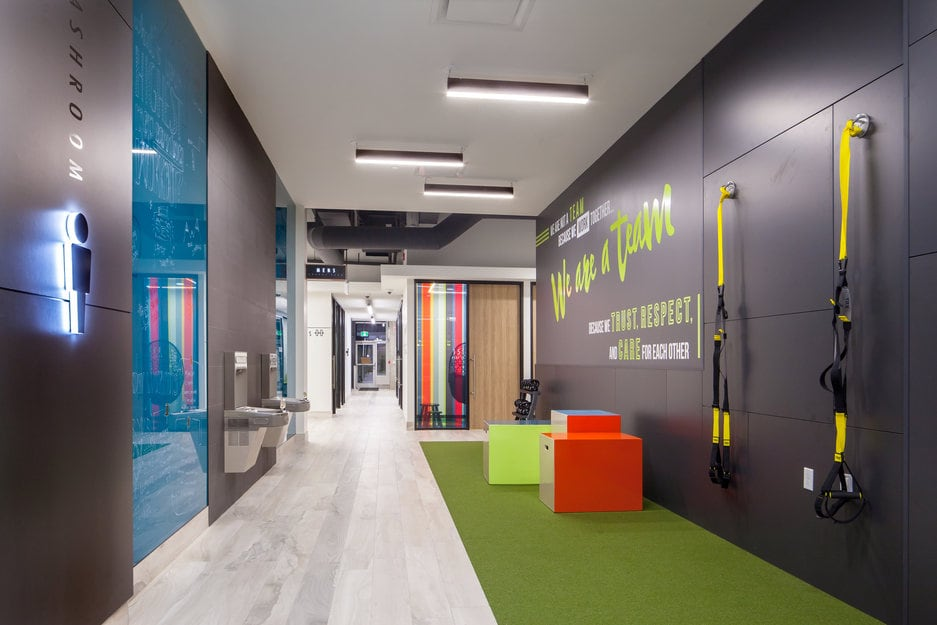 A green turf flooring installation / hardwood flooring installation at a fitness gym offices in Ontario. Green turf, grey hardwood, TRX Suspension Trainers, water fountains.