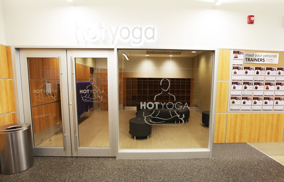 A sports fitness flooring installation at Hot Yoga in a Goodlife gym: rubber flooring in front and hardwood or hardwood-look LVT seen through front glass.