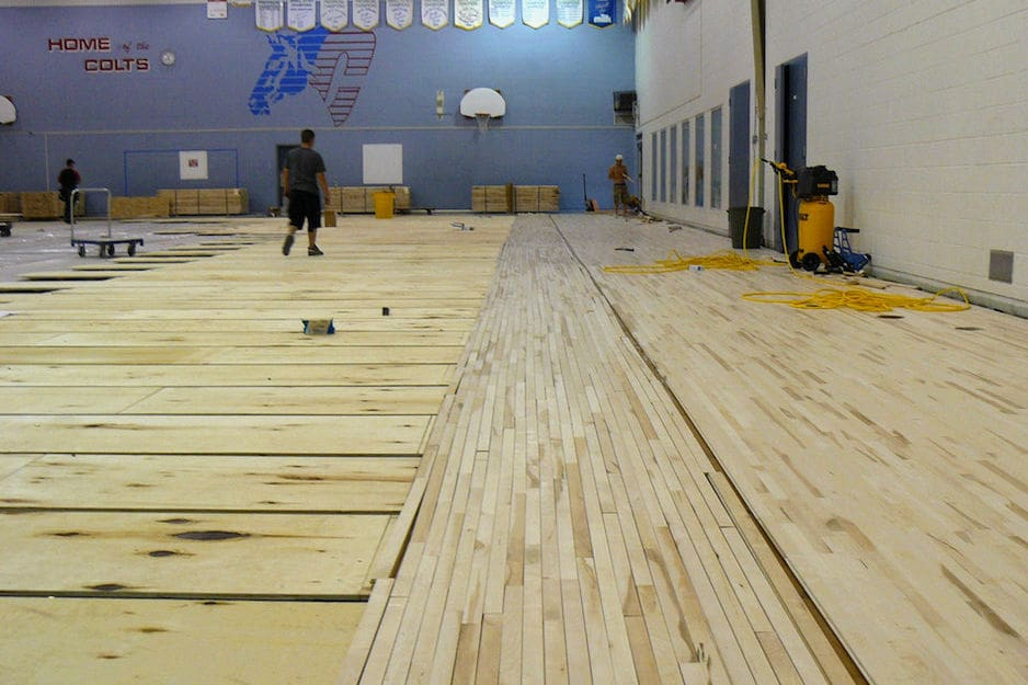 High school gymnasium with hardwood flooring under construction. Gym hardwood installation project.