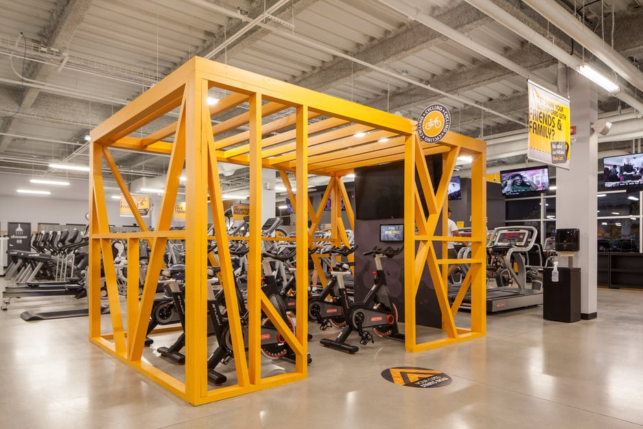 Concrete flooring at a Fit4Less gym. A London Ontario concrete flooring project. Photo features a cycle room space boxed in by open bright yellow framing upon the high polish concrete floor.
