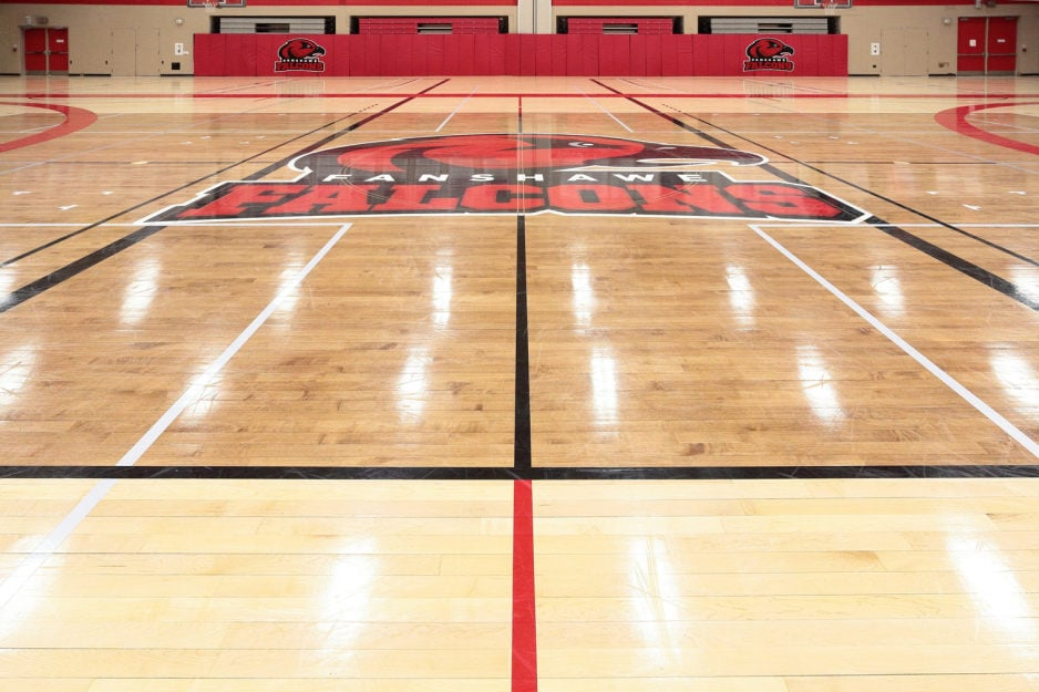 Gym flooring / court resurfacing project at Fanshawe College in London Ontario. Gym hardwood floor sanding, staining and refinishing to rival the big leagues with painting and masking services for game line markings and custom graphic artwork logos, wordmarks, mascot incorporated into the gym floor finish - Fanshawe College Falcons mascot logo in the centre.