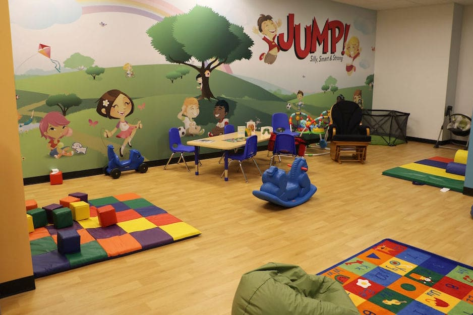 A flooring installation project in Ontario. Kids daycare room with natural light-coloured hardwood floors or hardwood looking LVT (luxury vinyl tile) floors and painted mural on the wall.