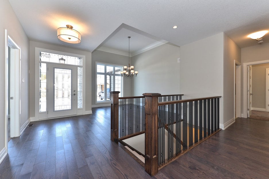 Dark hardwood flooring and traditional wood staircase leading to lower floor. New home entrance hallway. A hardwood flooring installation or hardwood refinishing project in London Ontario.