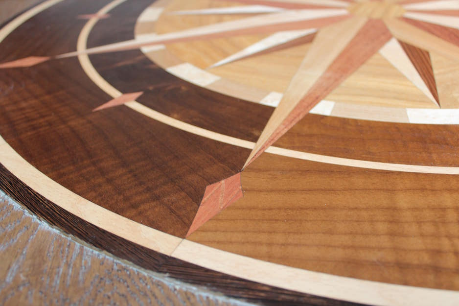 Hardwood flooring with a very intricate compass rose design with light, medium and dark wood elements composed together. A meticulously executed work of hardwood art. Part of a flooring project in London Ontario. A close up.