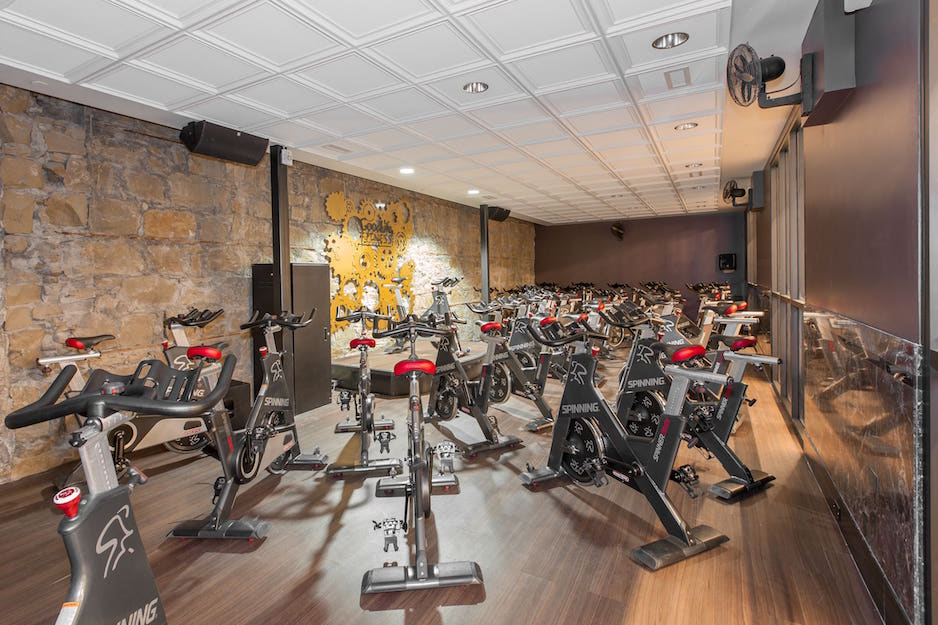 A gym flooring installation project. Goodlife gym cycling room with medium dark hardwood floors or LVT (luxury vinyl tile) and stone walls.