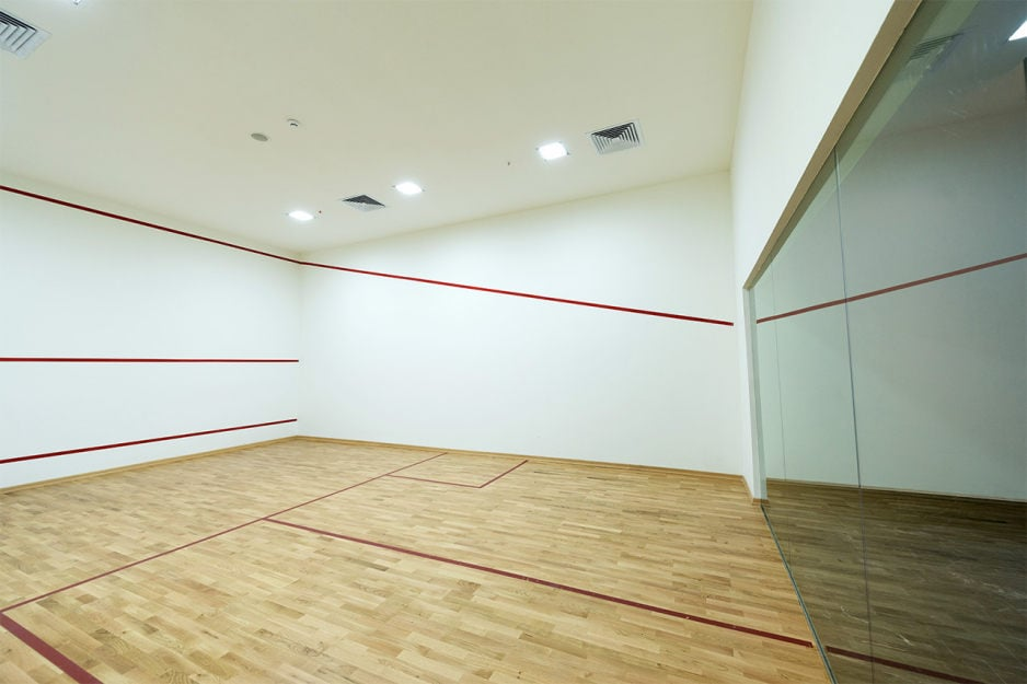 A squash court and court flooring installation project in London Ontario. Squash court room with hardwood floor, glass backwall, white ceiling and specially constructed walls with line graphic work.