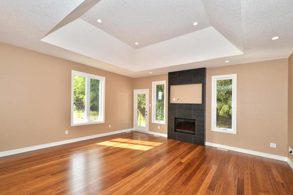 A hardwood flooring installation or wood floor refinishing project in London Ontario. Mixed light and dark brown hardwood floors in an white-trimmed and beige-walled fireplace room.