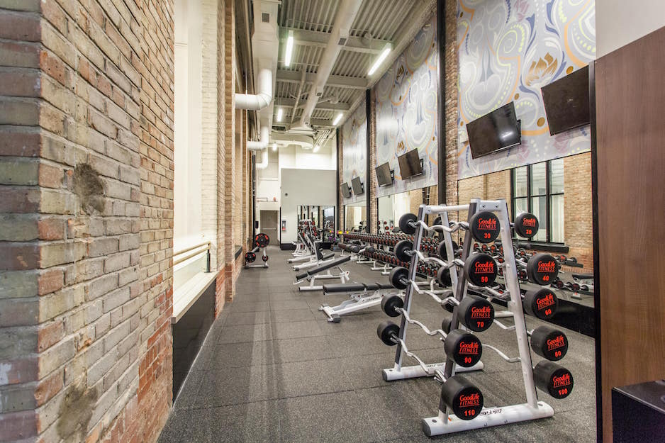 Gym flooring installation in Toronto Ontario. Goodlife gym weight and dumbbell room with rubber flooring, brick walls, and flat screen televisions.